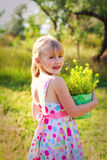 Smiling little girl with a bucket of flowers in the park Royalty Free Stock Image