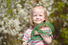 Smiling little girl with a butterfly net Royalty Free Stock Photography
