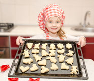 Smiling little girl in chef hat with baking sheet of cookies Royalty Free Stock Image