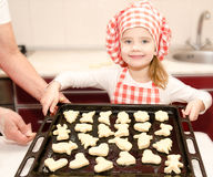 Smiling little girl in chef hat with baking sheet of cookies Royalty Free Stock Photography
