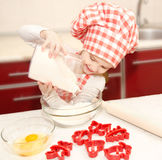 Smiling little girl with chef hat put flour for baking cookies Royalty Free Stock Photo