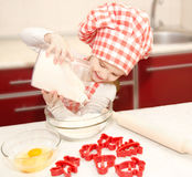 Smiling little girl with chef hat put flour for baking cookies Royalty Free Stock Image