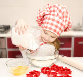 Smiling little girl with chef hat put flour for baking cookies Stock Images