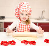 Smiling little girl with chef hat rolling dough Royalty Free Stock Photo