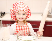 Smiling little girl with chef hat and rolling  pin Royalty Free Stock Images