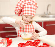 Smiling little girl with chef hat stirrring cookie dough Royalty Free Stock Images