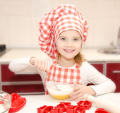 Smiling little girl with chef hat stirrring cookie dough Stock Photo