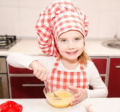 Smiling little girl with chef hat stirrring cookie dough Stock Photos