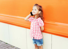 Smiling little girl child talking on smartphone in city Stock Photos
