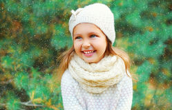 Smiling little girl child wearing a knitted hat sweater with scarf near christmas tree Stock Image