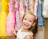 Smiling little girl chooses a dress from the wardrobe Royalty Free Stock Images