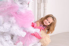 Smiling little girl at christmas tree indoors Royalty Free Stock Image