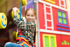 Smiling little girl on climbing wall Royalty Free Stock Image