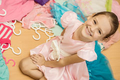 Smiling little girl among clothes hangers Stock Images