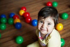 Smiling little girl and colorful balls around stock image