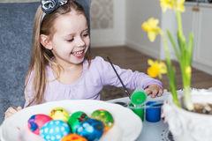 Smiling little girl coloring easter eggs Royalty Free Stock Images