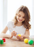 Smiling little girl coloring eggs for easter Stock Image