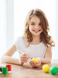 Smiling little girl coloring eggs for easter Royalty Free Stock Image