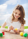 Smiling little girl coloring eggs for easter Stock Photography
