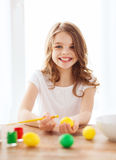 smiling little girl coloring eggs for easter Royalty Free Stock Photos