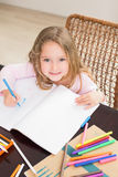 Smiling little girl colouring at the table Stock Photo