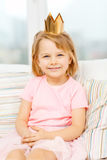 Smiling little girl in crown sitting on sofa Royalty Free Stock Images