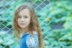 Smiling little girl with curly hair near fence of grid Stock Image