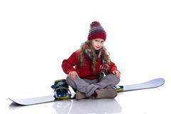 Smiling little girl with curly hairstyle wearing knitted sweater, scarf, hat and gloves sitting on blue snowboard, isolated Royalty Free Stock Photography