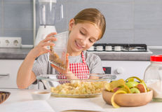 Smiling little girl with cut apples in bowl Stock Photo