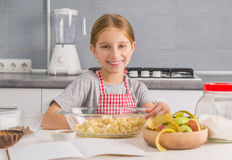 Smiling little girl with cut apples in bowl royalty free stock images