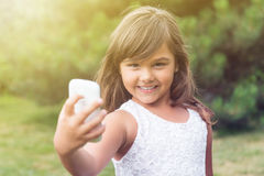 Smiling little girl doing selfie is looking at the camera Stock Images