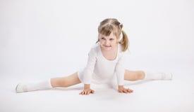 Smiling little girl doing the splits Stock Image