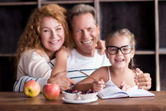 Smiling little girl drawing with her grandparents Stock Images