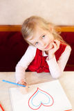 Smiling little girl draws heart. Valentine's Day. Smiling little girl draws heart in an album. Valentine's Day Stock Photo