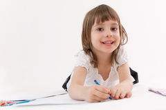 Smiling little girl draws a picture. Stock Images