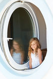Smiling little girl in dress look into window Royalty Free Stock Photography