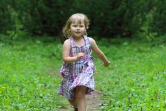 Smiling little girl in dress runs at summer day. In green park Stock Images
