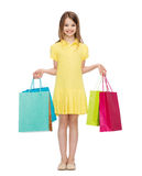 Smiling little girl in dress with shopping bags Stock Image