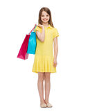Smiling little girl in dress with shopping bags Stock Photo