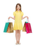 Smiling little girl in dress with shopping bags Royalty Free Stock Photo