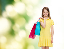 Smiling little girl in dress with shopping bags Royalty Free Stock Photos