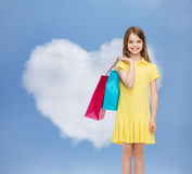 Smiling little girl in dress with shopping bags Stock Images