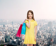Smiling little girl in dress with shopping bags Royalty Free Stock Photography
