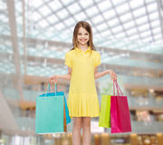 Smiling little girl in dress with shopping bags Stock Photos