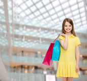 Smiling little girl in dress with shopping bags Stock Photography