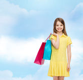 Smiling little girl in dress with shopping bags Royalty Free Stock Image