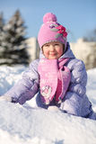 Smiling little girl dressed in pink scarf looks away Royalty Free Stock Photo