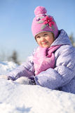 Smiling little girl dressed in pink scarf sits on snow Royalty Free Stock Photo