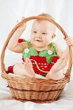 Smiling little girl dressed in strawberry suit sitting in basket Stock Image