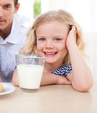 Smiling little girl drinking milk Stock Image